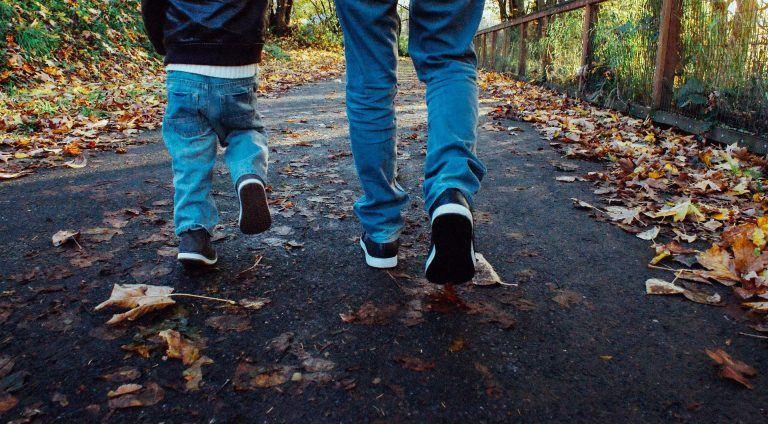 רגליים של ילד ומבוגר הולכים בשביל עם עלים