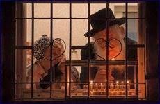 זוג מבוגרים מבעד לחלון מדליקים נרות חנוכה