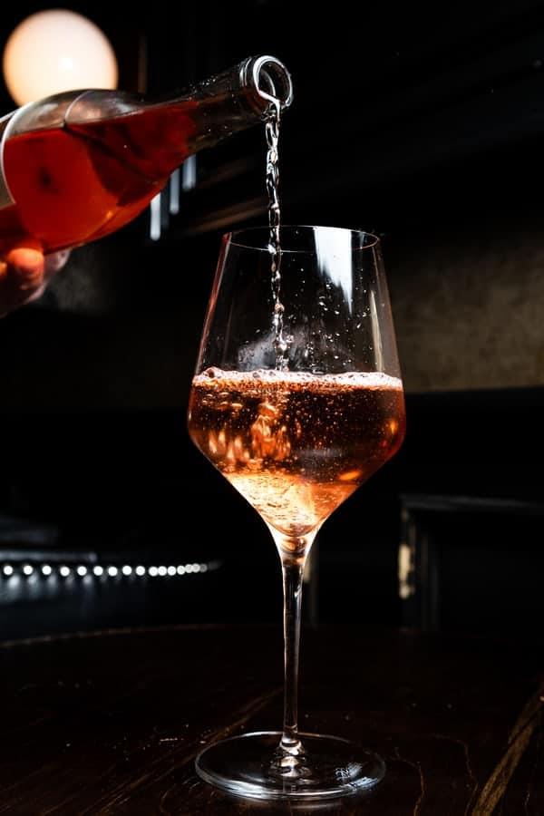 בקבוק יין נמזג לכוס יין
