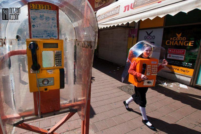 ילדה מחופשת לטלפון ציבורי ליד טלפון ציבורי