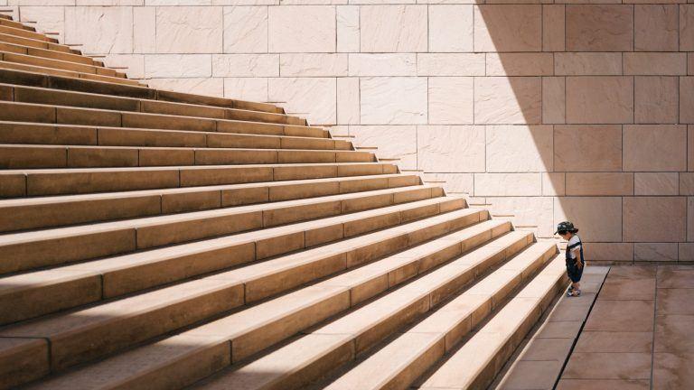 ילד קטן עומד בקצה של גרם מדרגות ארוך ורחב