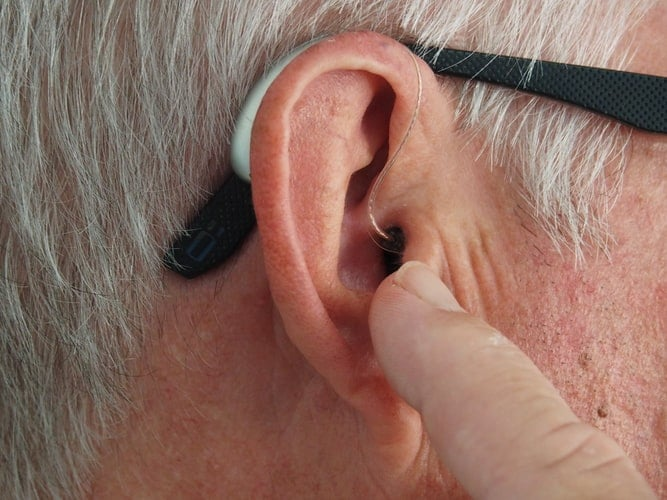 אדם מצביע אל האוזן שלו